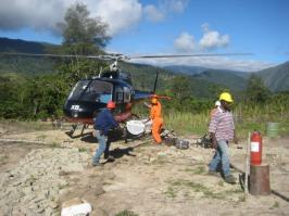 An image of workers and a helicopter in a remote site