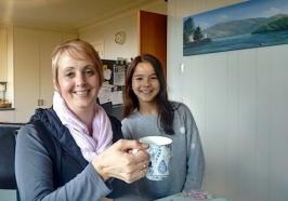 Student and parent holding a cup of tea