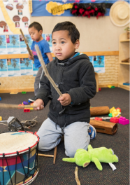 Student playing with drum.