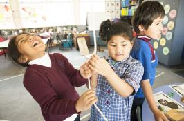 Primary students holding string and laughing.