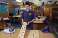 Student showing wood with holes cut in it for lightness
