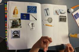 student sticking kitchen items in workbook as technological systems