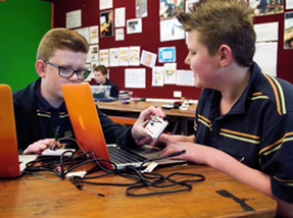 Two students working together with computers and electronics programming