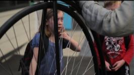 Primary student looks at old bike wheel
