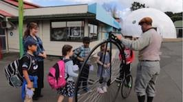 Teacher and a group of students looking at an old style bicycle