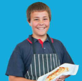 A student wearing an apron and holding bread he has made