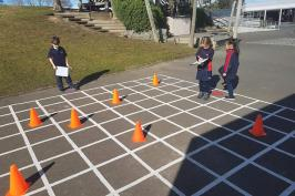 Students writing instructions to move through a grid painted outdoors