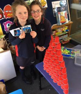 Two students with their tower made using plastic cups