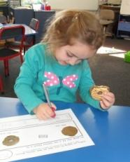 Student writing and holding cookie