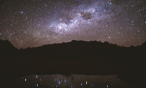 Night sky full of stars above mountains and reflected in a lake